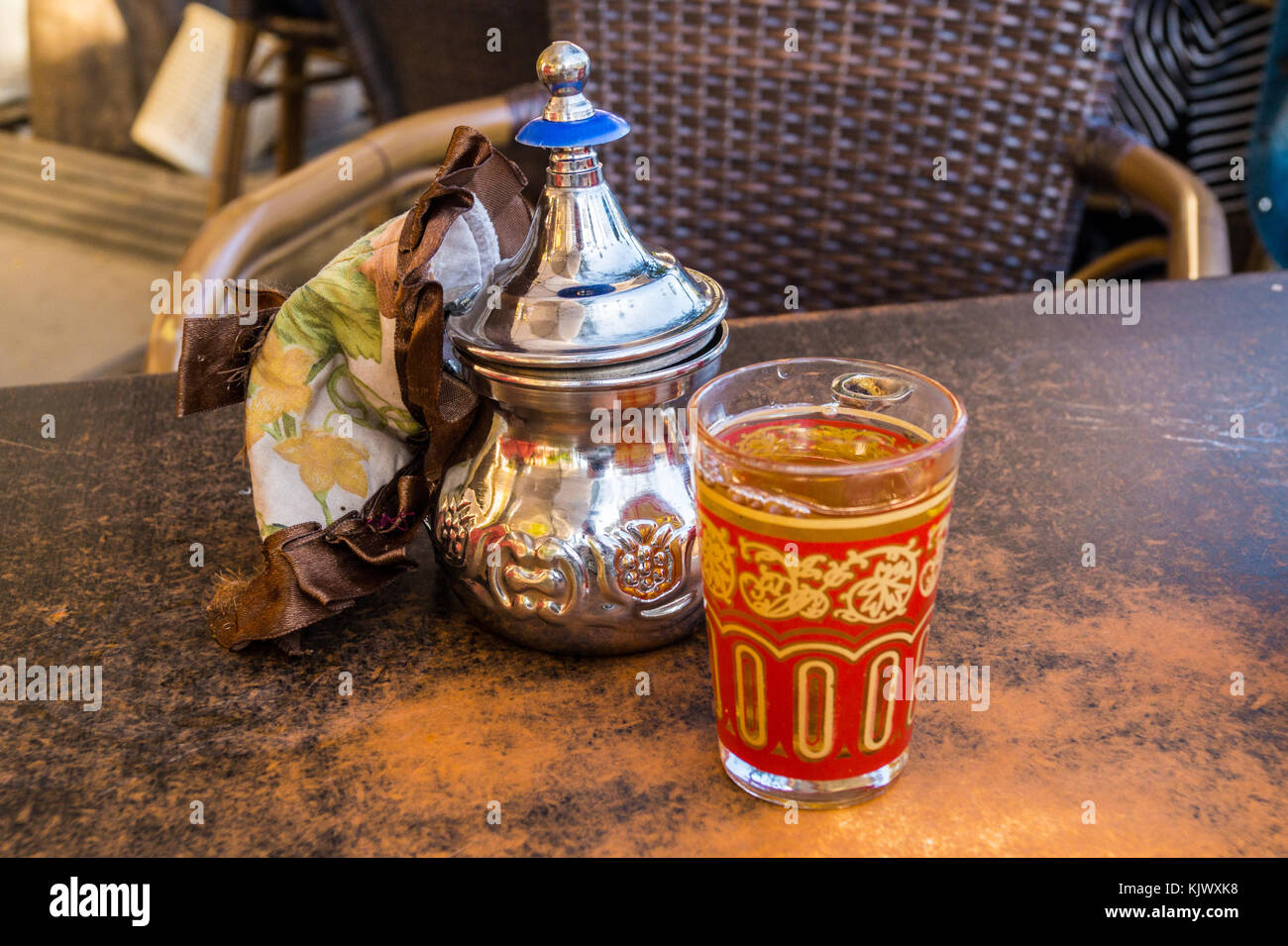 Mint tea in a teapot and decorated glass on a teahouse table, Seville, Andalucia, Spain Stock Photo