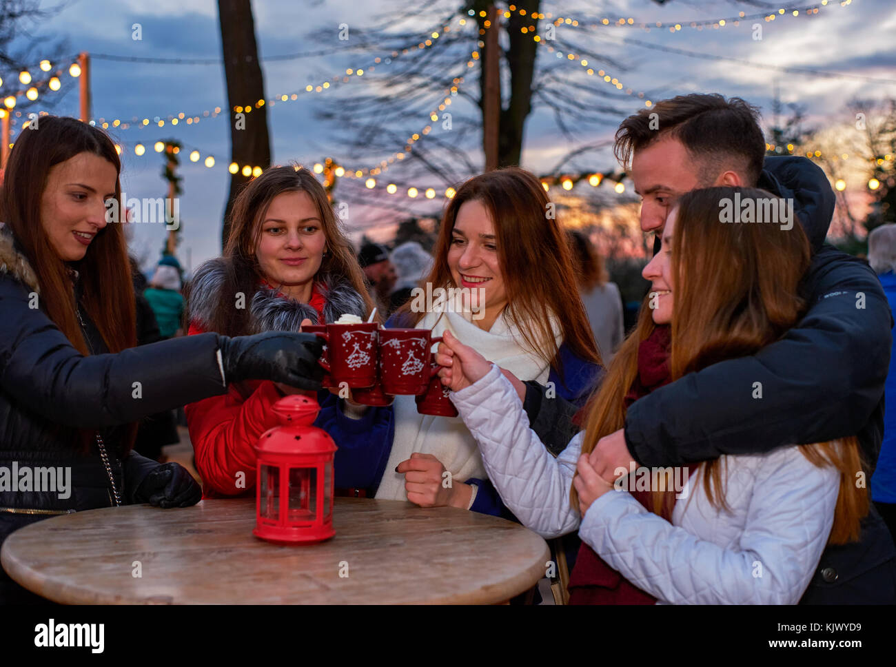 Five young people drinking mulled wine at Christmas market - Stock Image