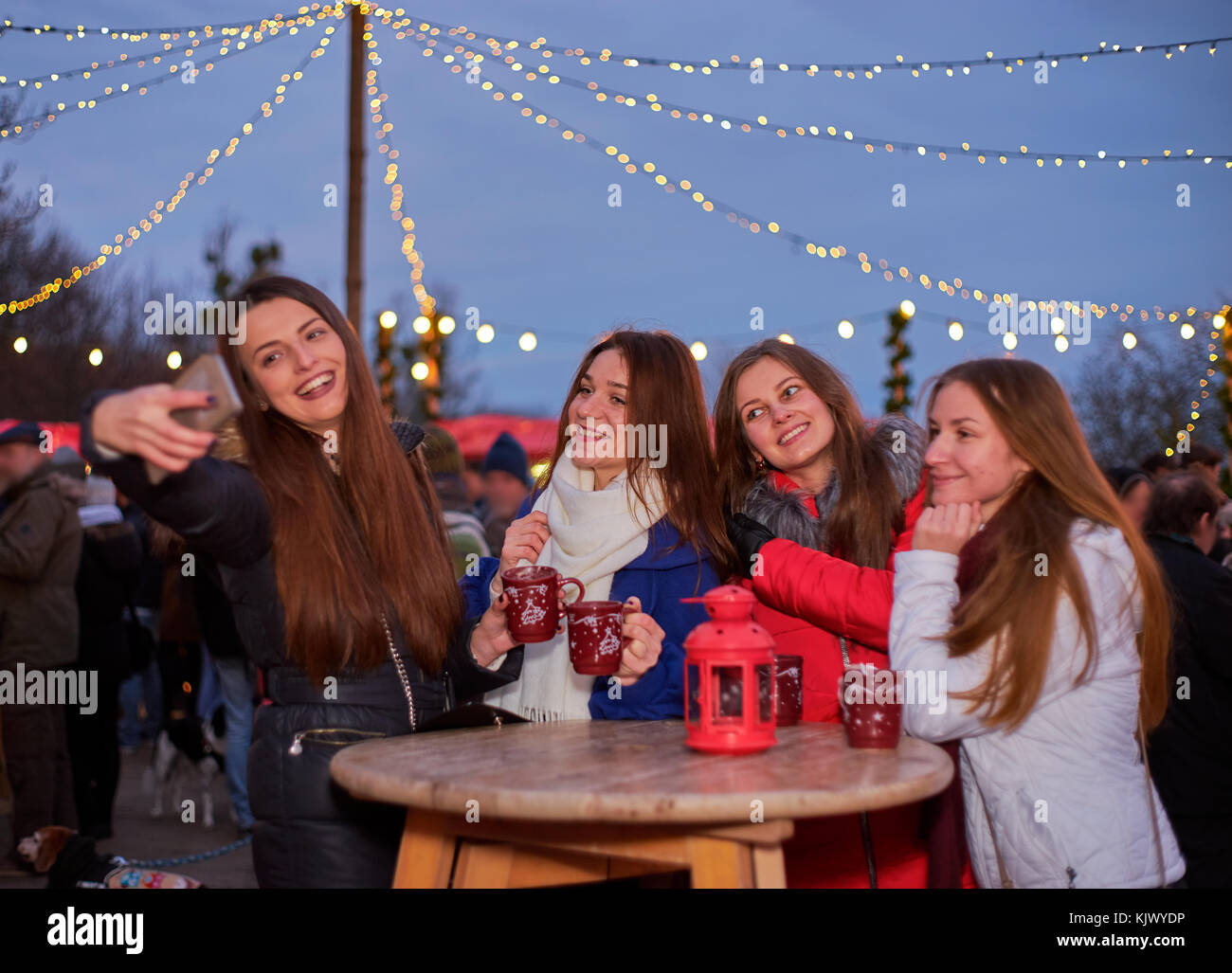 Four young woman making photos at Christmas market - Stock Image