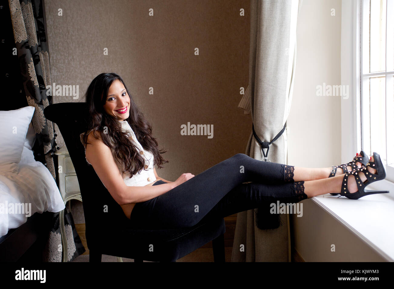 Beautiful brunette girl wearing black leggings in a bedroom location - Stock Image