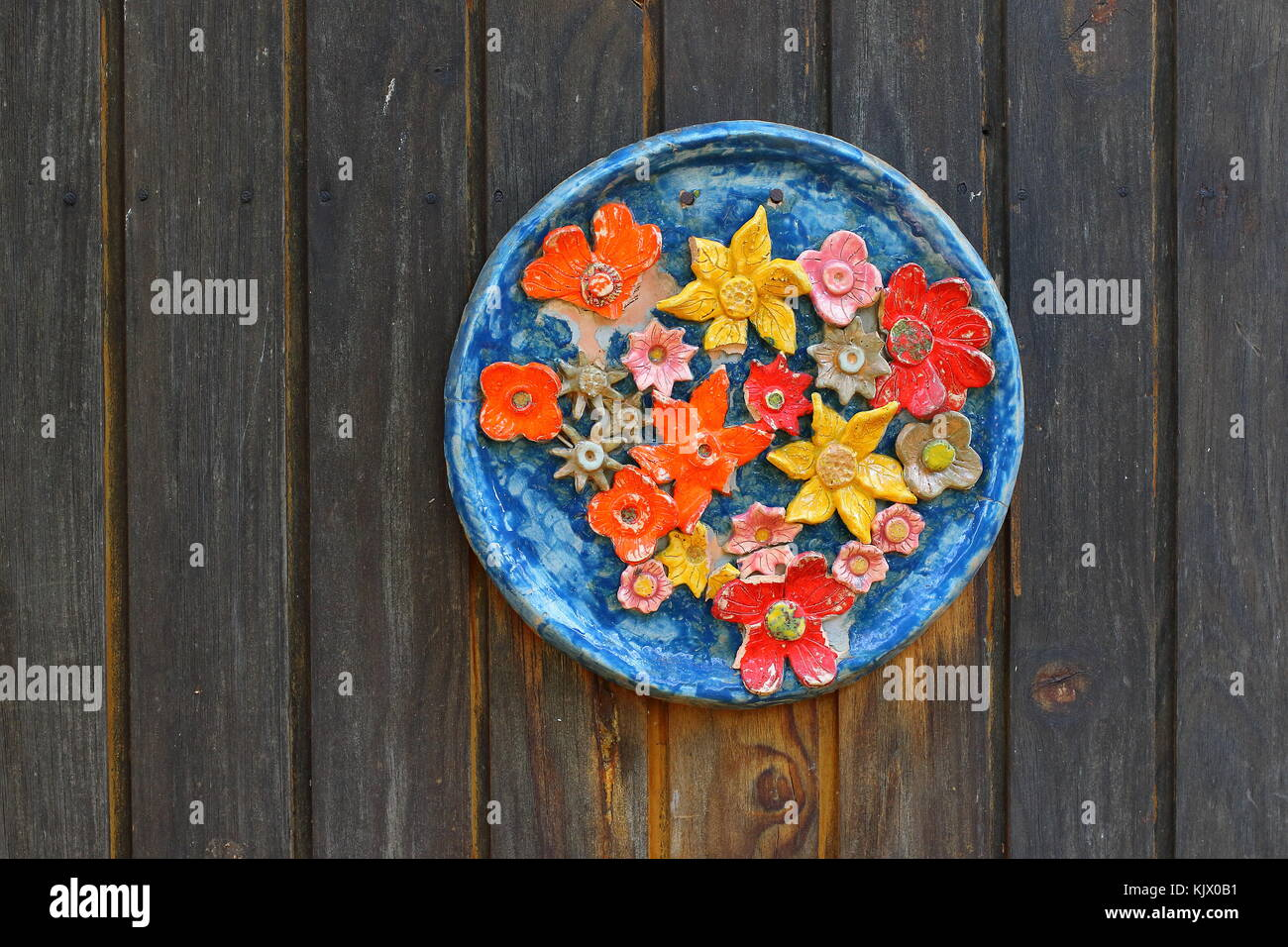 For background use - a faded and damaged ceramic plate with a colorful flower motif on a weathered wooden wall with - Stock Image