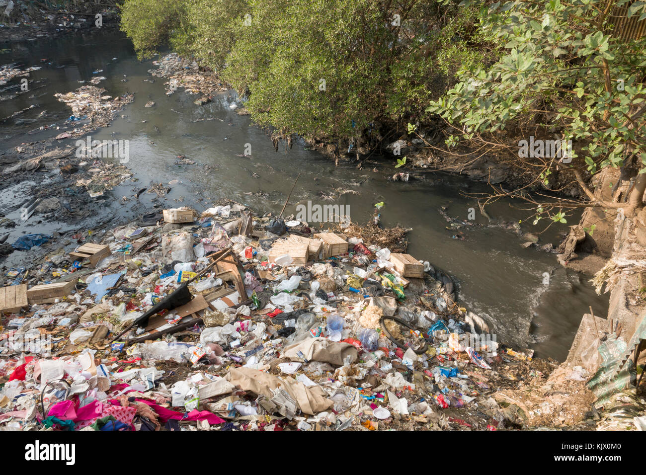 Plastic bags, household waste and sewage create heavy pollution in river at Juhu, Mumbai - Stock Image