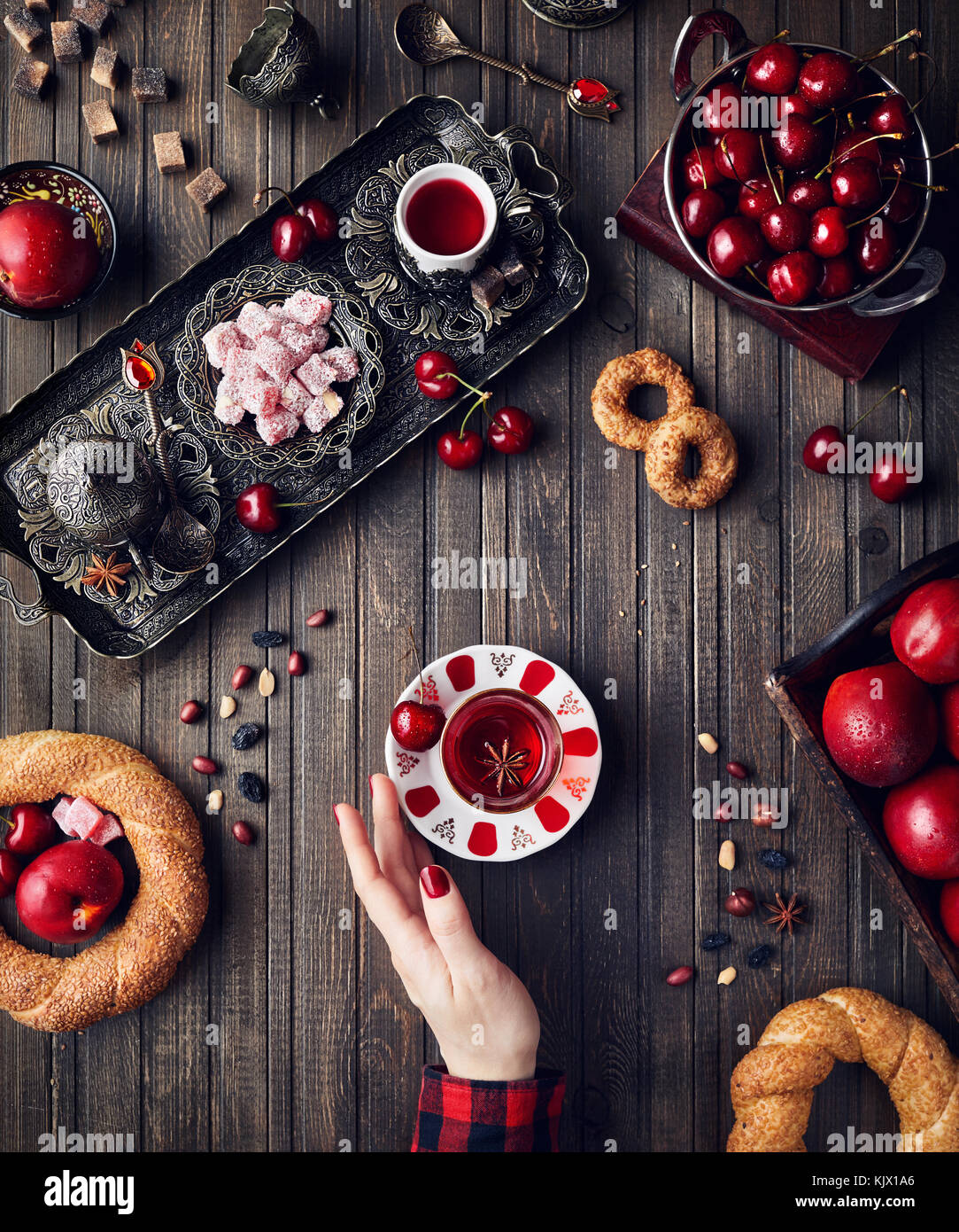 Woman touching red tea near Turkish delights rahat lokum, simits and fruits on wooden table - Stock Image