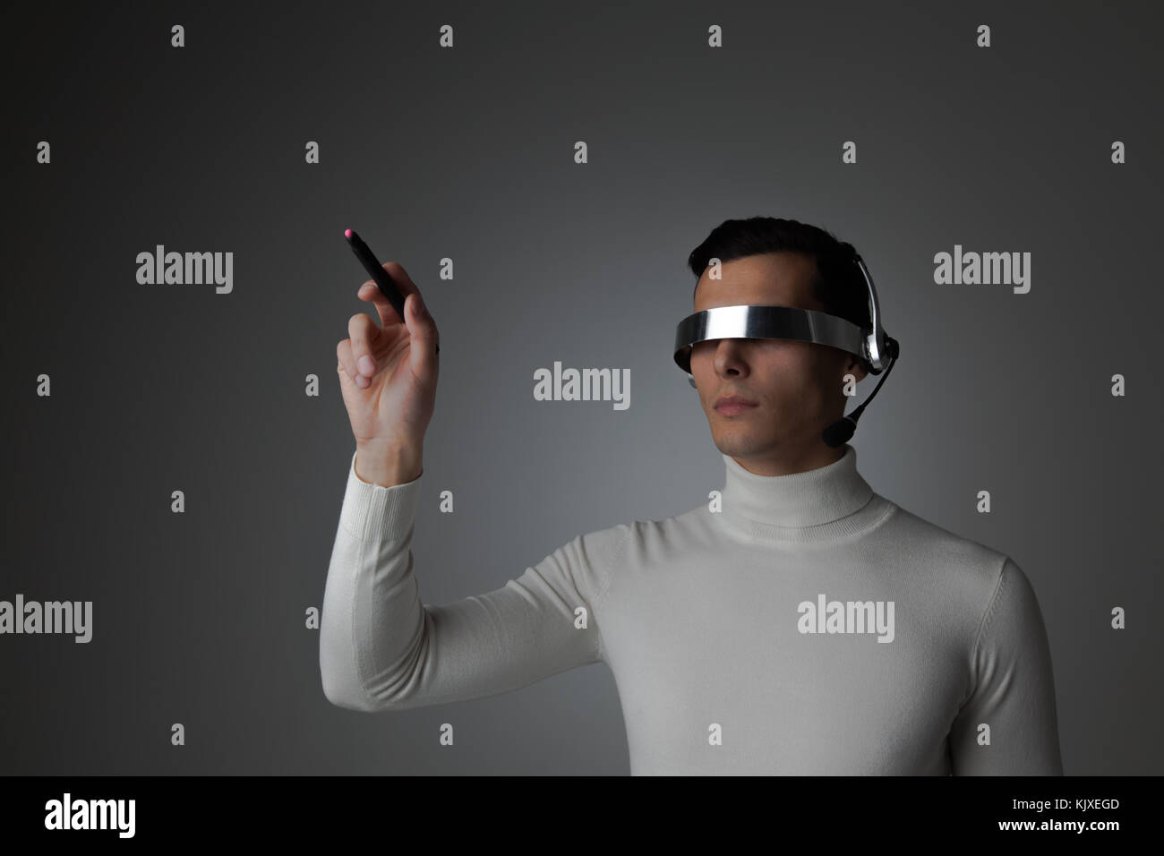 Man using futuristic VR goggles headset with microphone and touching virtual screen with digital pen - Stock Image