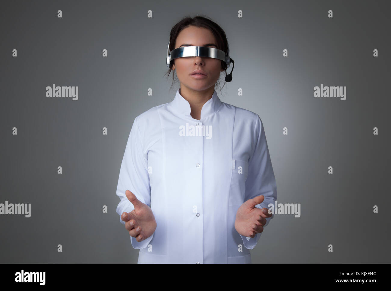 Female scientist or doctor using futuristic VR goggles headset with microphone and holding virtual object - Stock Image