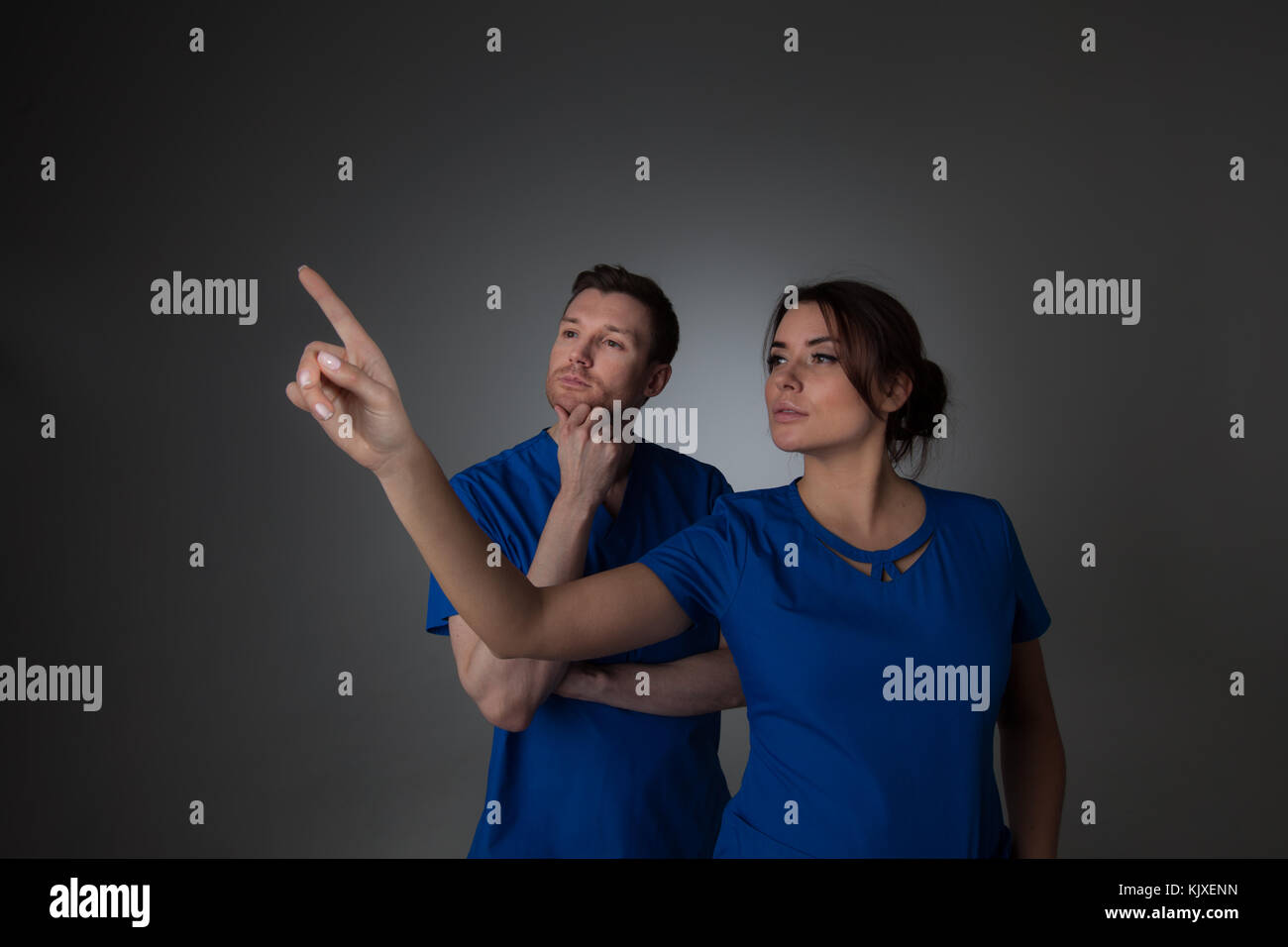 Healthcare, medicine and technology concept - two doctors pointing to something or pressing imaginary button - Stock Image