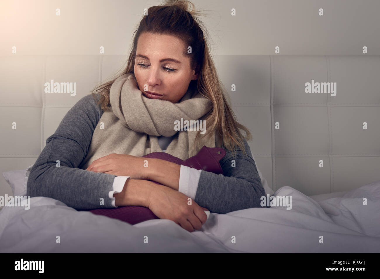 Sick woman wrapped in a warm scarf and clutching a hot water bottle sitting using nasal spray with a miserable expression - Stock Image