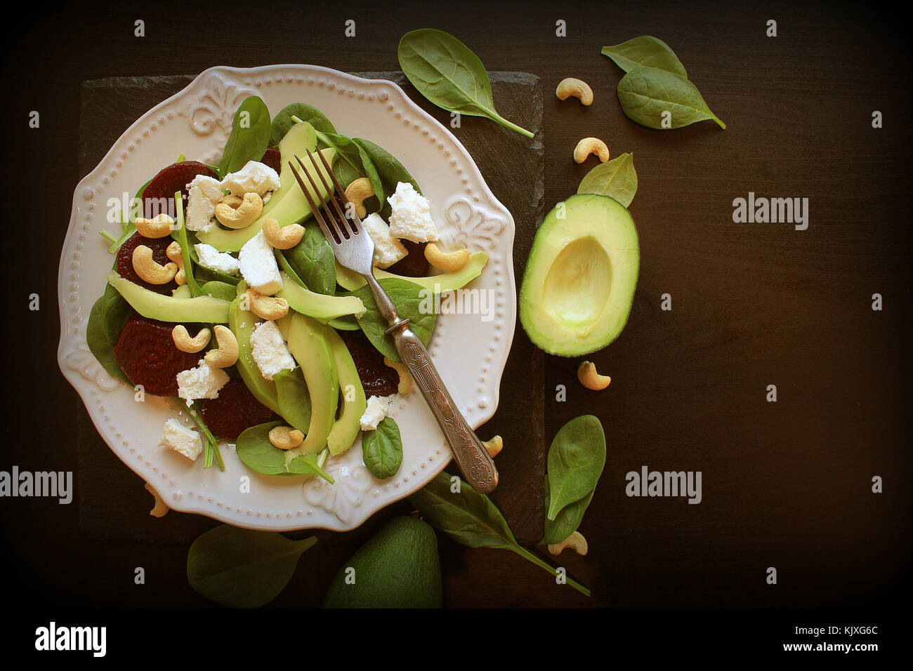 Healthy beet salad with fresh sweet baby spinach, nuts, feta cheese and avocado. Plate with salad on dark table. - Stock Image