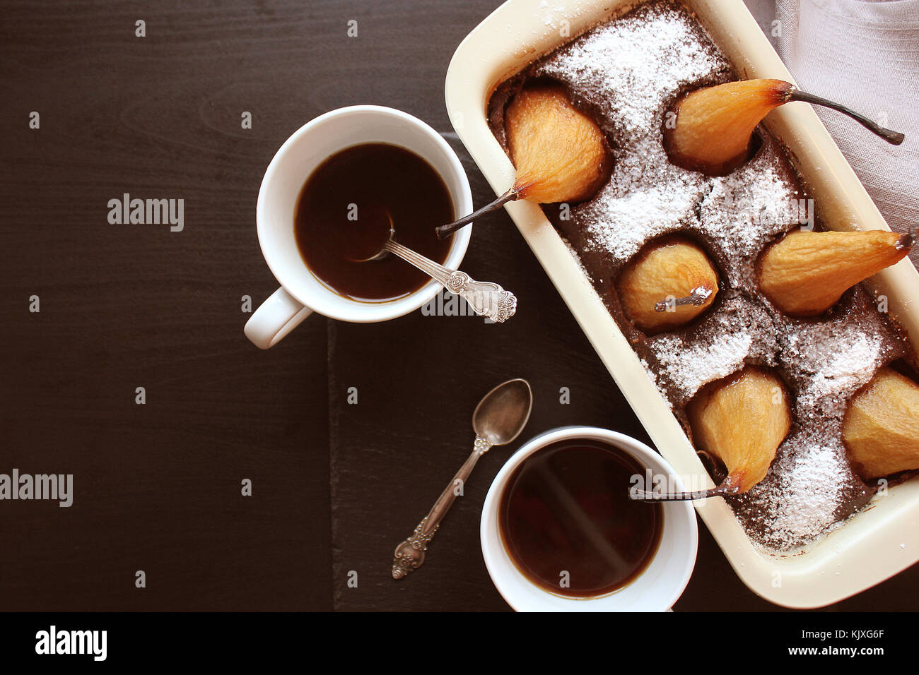 Chocolate loaf cake with whole pears baked inside and two cups coffee on dark background. Top view - Stock Image