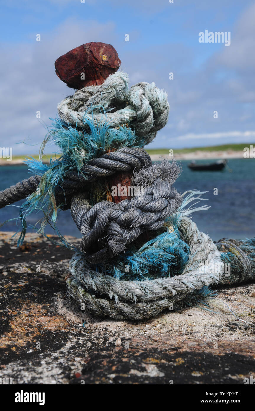 Knotted rope on an iron stanchion on a harbour with traditional Irish Curragh in the background Stock Photo