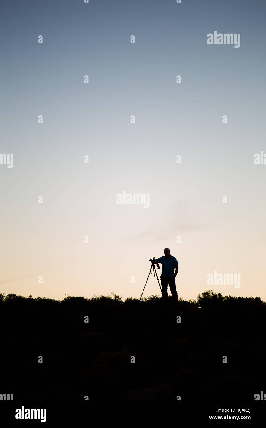 Silhouette of a photographer with his tripod on a hill with dawn setting in. - Stock Image