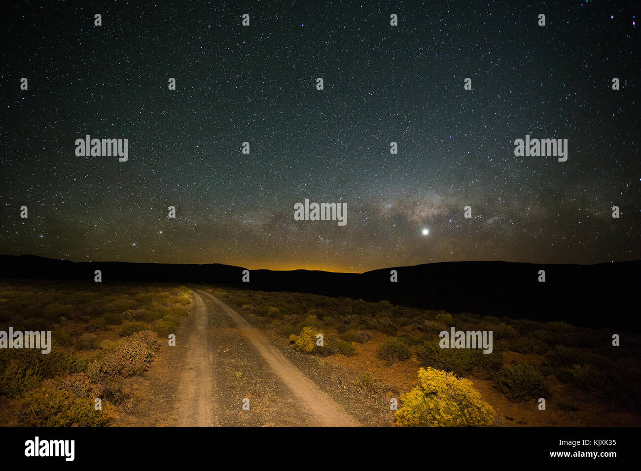 Wide angle view of a two track road in the Karoo at night with the milky way in the sky - Stock Image
