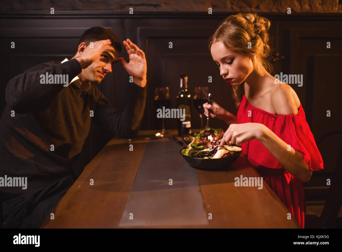 a3f83508b5336 Quarrel of young couple in restaurant, bad evening. Elegant woman in red  dress and her man eating in cafe