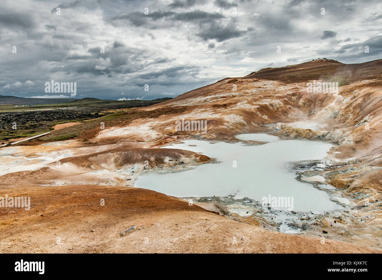 The solfatares create a milky pond on the orange and mineral slopes of the Krafla volcano - Stock Image