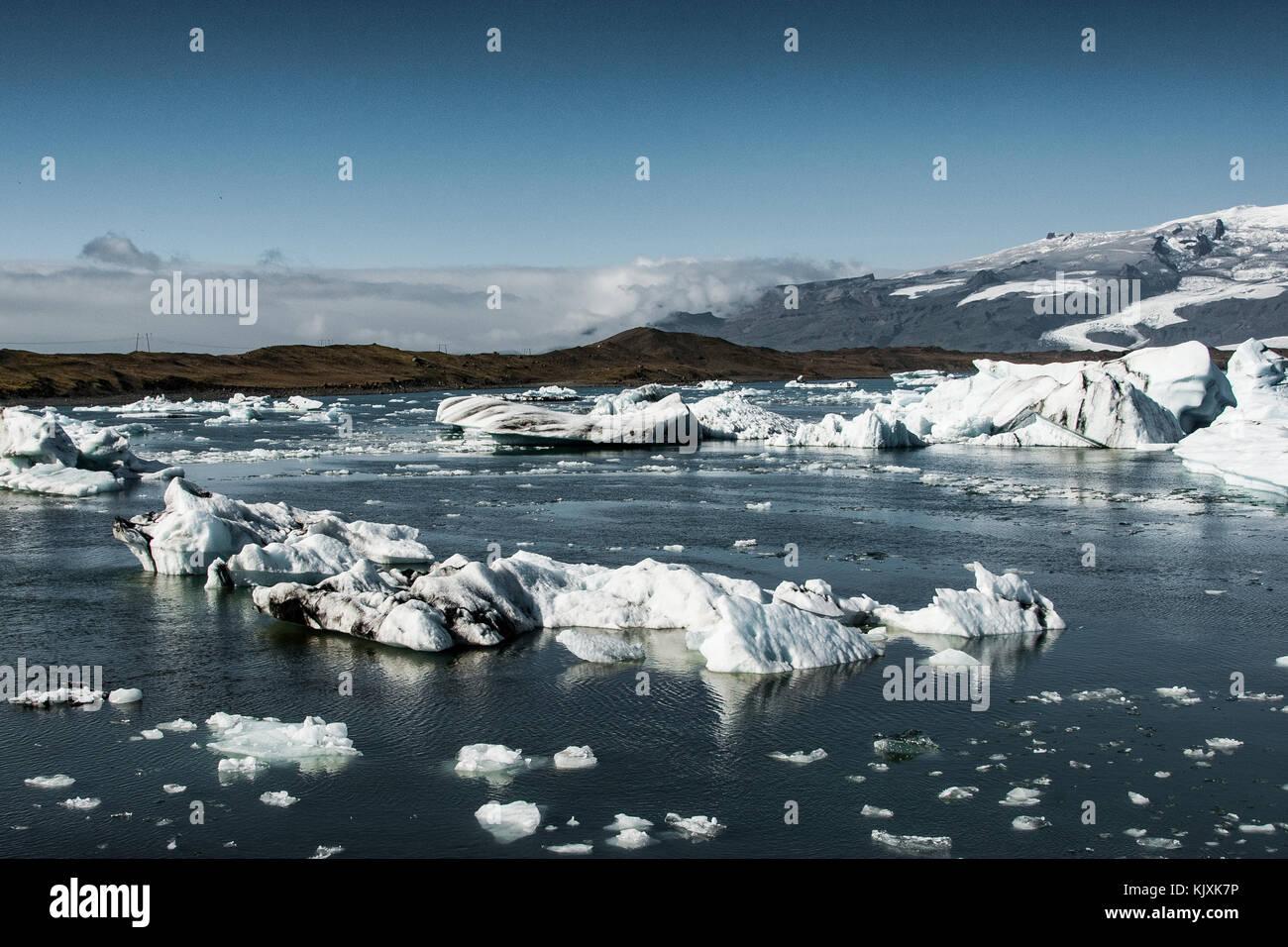 Groups of icebergs drift on the lake lagoon formed by the melting of the Jokulsarlon glacier - Stock Image
