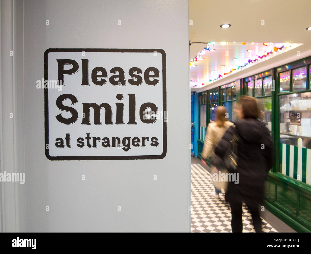 A notice requesting that people smile at each other - Stock Image