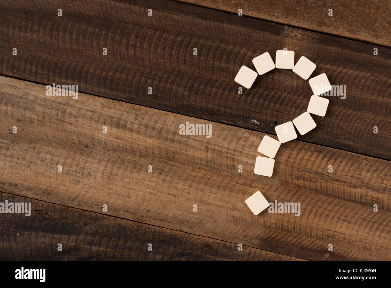 tiles arranged forming question mark. question mark on wooden table background - Stock Image