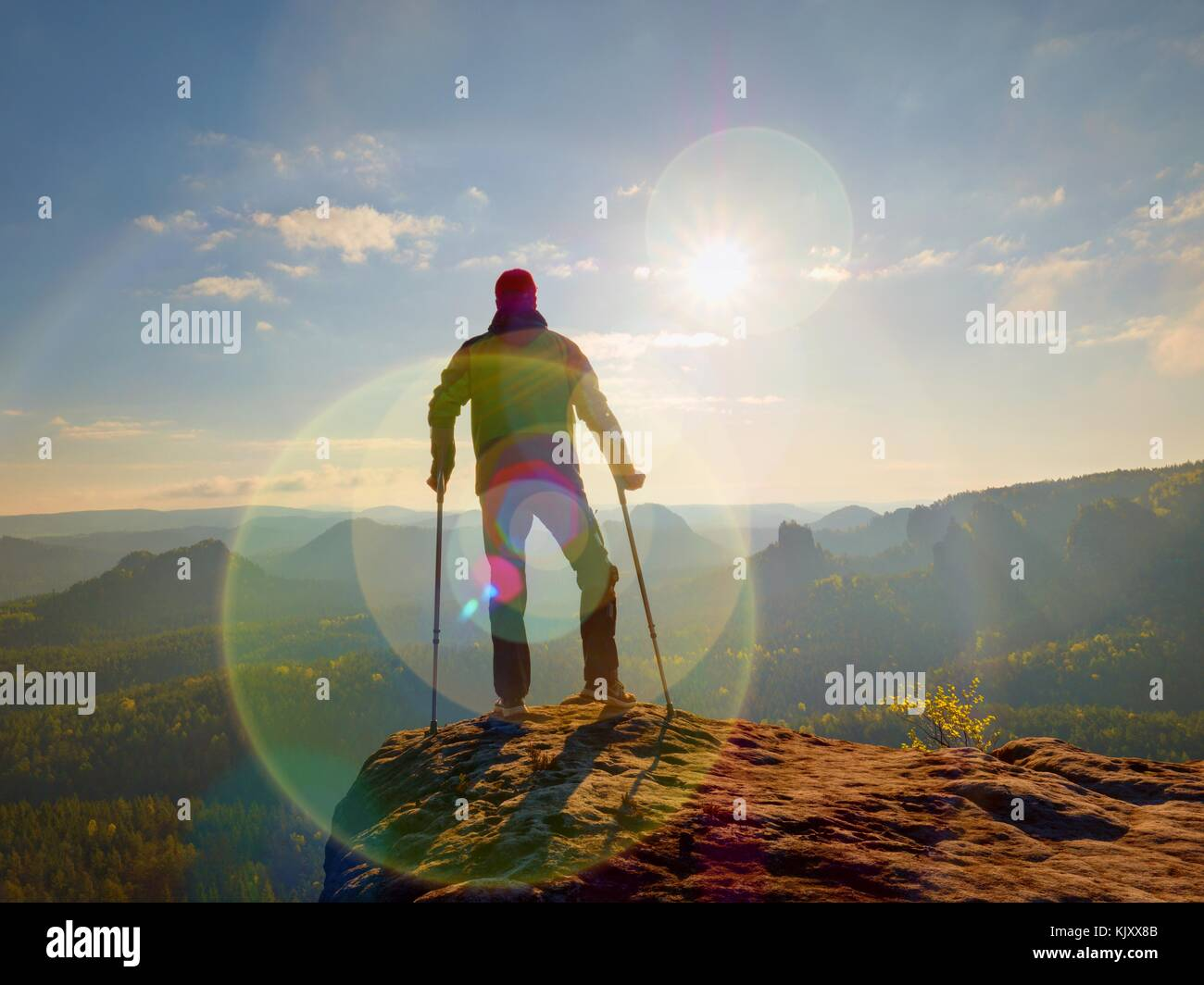Tourist with  forearm crutch above head  on trail. Hurt hiker achieved mountain peak with broken knee in immobilizer. - Stock Image