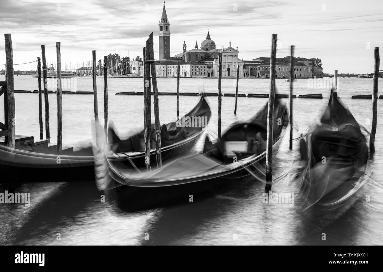 Gondoliers float in the canals of Venice in the early morning prior to a days work. - Stock Image