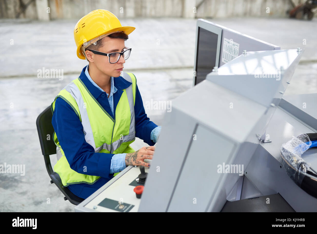 Concentrated factory employee in green waistcoat using technical machine while working on operator dashboard at - Stock Image