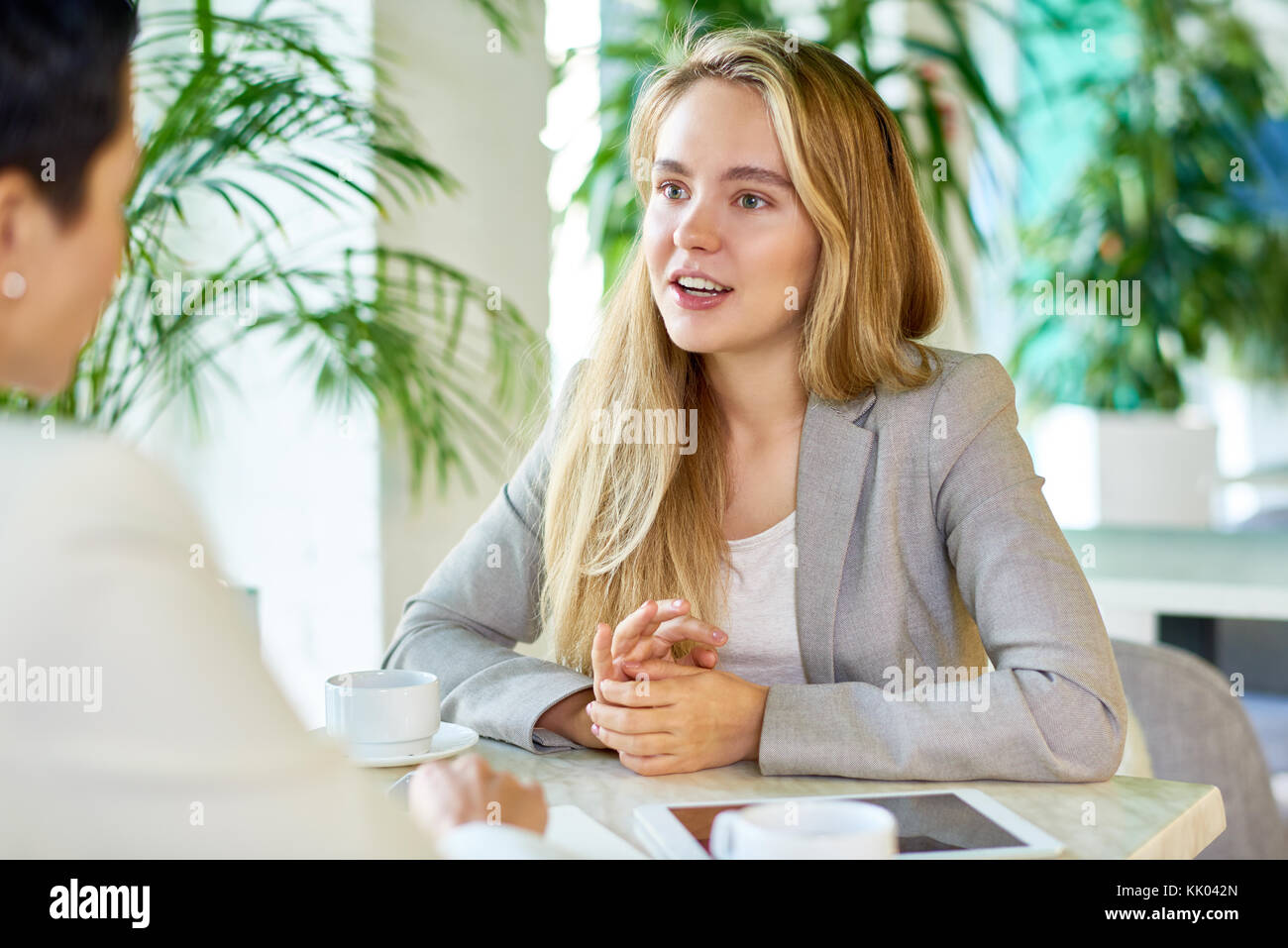 Portrait of two modern young women discussing work sitting at table in cafe during business meeting, focus on young - Stock Image