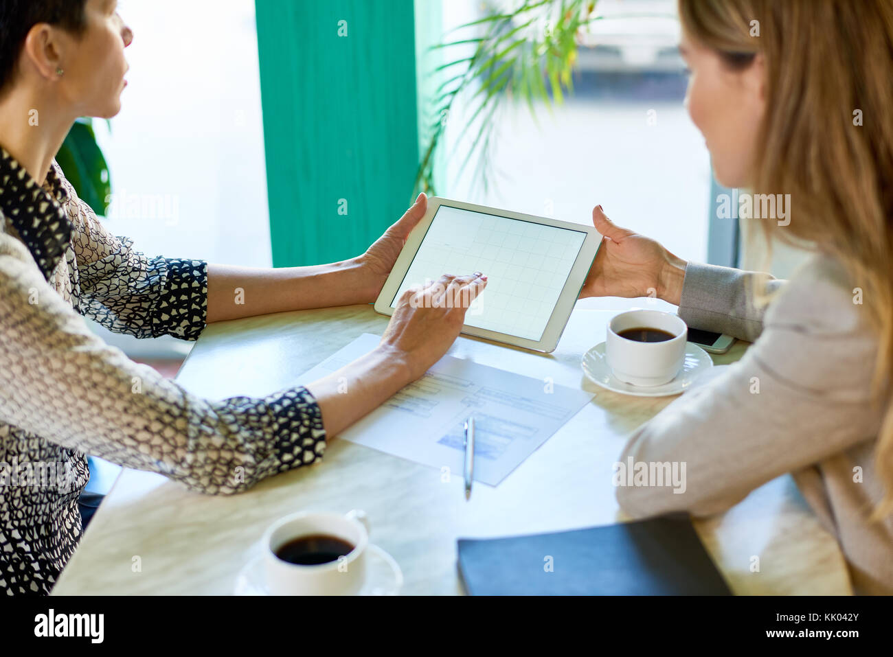 High angle view of two modern unrecognizable women  working at table in cafe using digital tablet during business - Stock Image