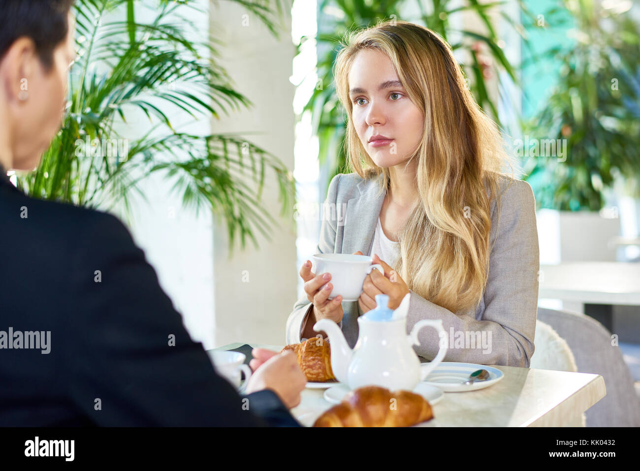 Portrait of modern young woman drinking coffee at cafe table listening to someone sitting across from her during - Stock Image