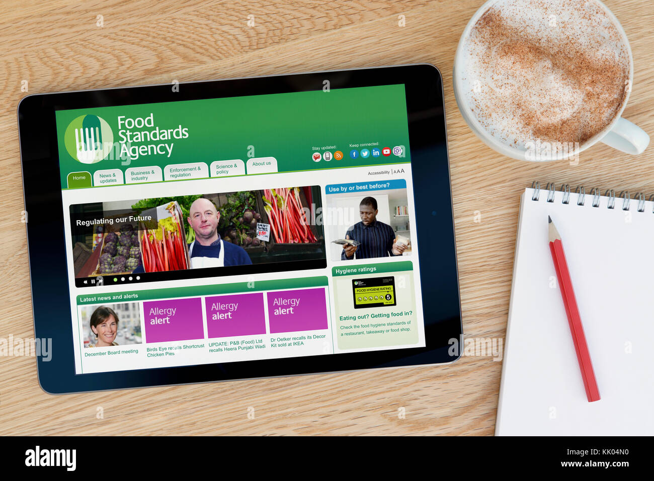 A man looks at the Food Standards Agency website on his iPad tablet device, shot against a wooden table top background - Stock Image