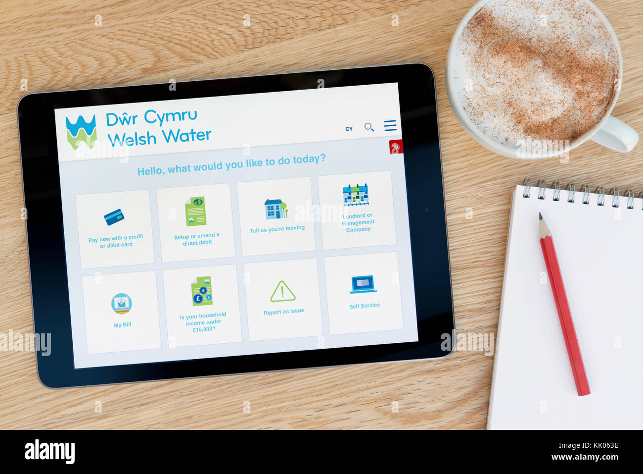 A man looks at the Welsh Water website on his iPad tablet device, shot against a wooden table top background (Editorial - Stock Image