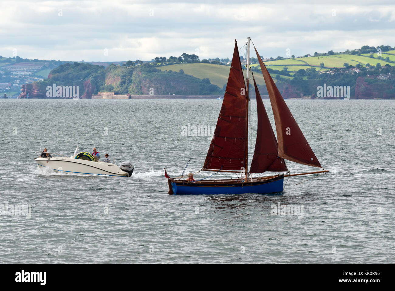 A lone yachtsman sailing into the entrance of the River Exe at Exmouth on the south Devon Coast on a calm summers - Stock Image