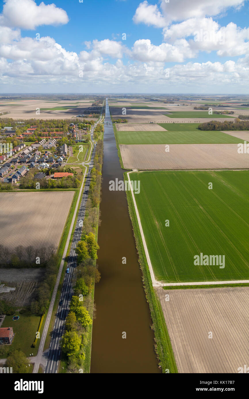 Long straight canal next to road, near Amsterdam, North Holland, The Netherlands Stock Photo
