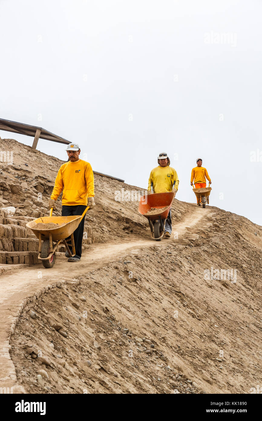 Three local Peruvian workmen with wheelbarrows working on restoration of the pre-Inca ruins at Huaca Pucllana or - Stock Image