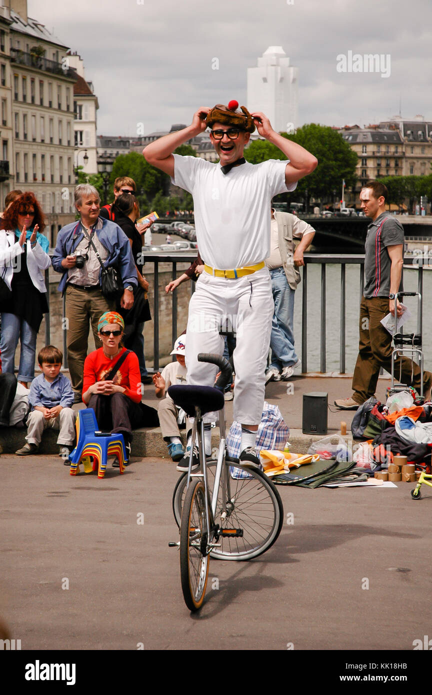 Street performer entertain tourists on the The pont Saint-Louis bridge across the River Seine beside Notre-Dame Stock Photo