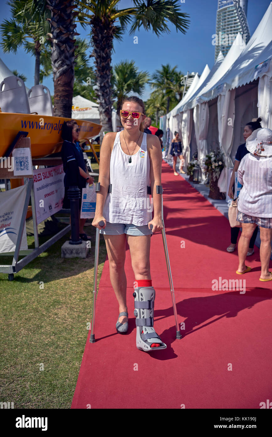 Young woman with crutches and wearing a medical boot after a foot injury. - Stock Image