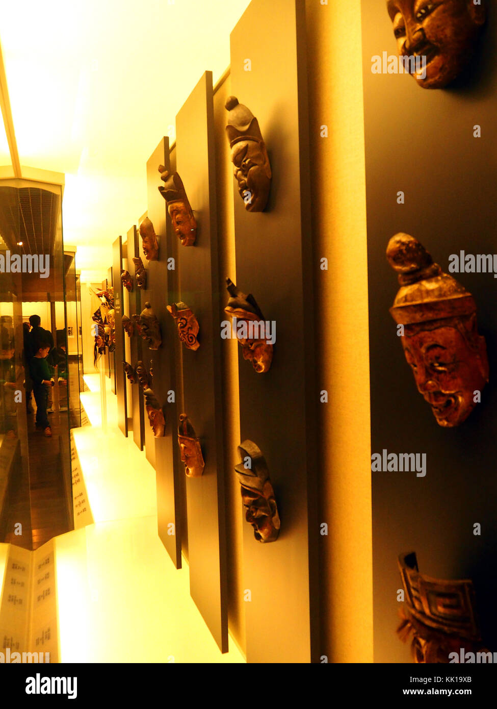 Young boy looking at the gallery of masks in the Shanghai Museum, China - Stock Image