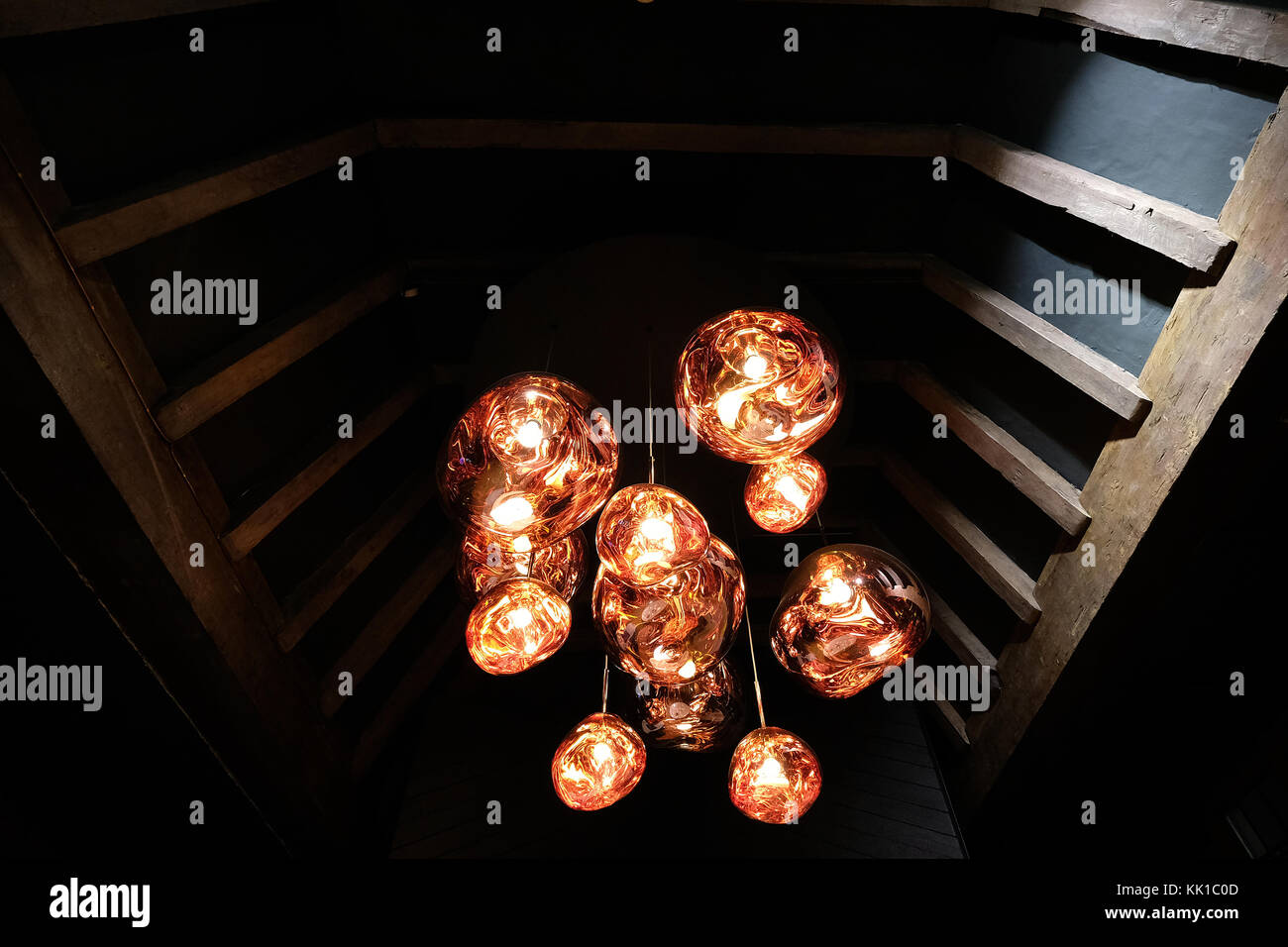 Tom Dixon copper colour 'Melt' pendant lights hanging in the Liberty of London store, London UK. Photographed November Stock Photo