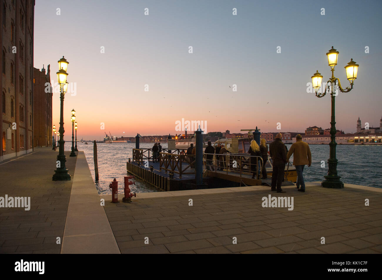 Vaporetto landing at dusk from Giudecca towards Dorsoduro in Venice - Stock Image