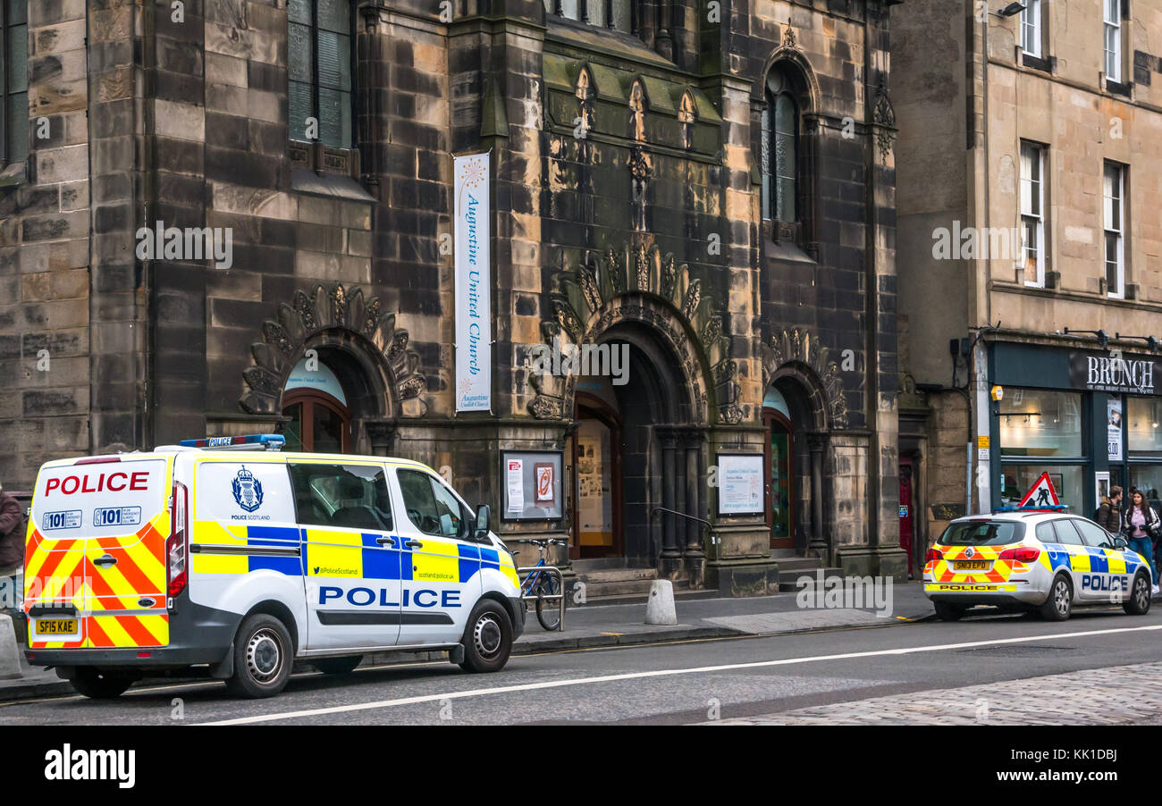 Police van and police car parked on George IV Bridge, outside St Augustine United Church, Edinburgh, Scotland, UK - Stock Image