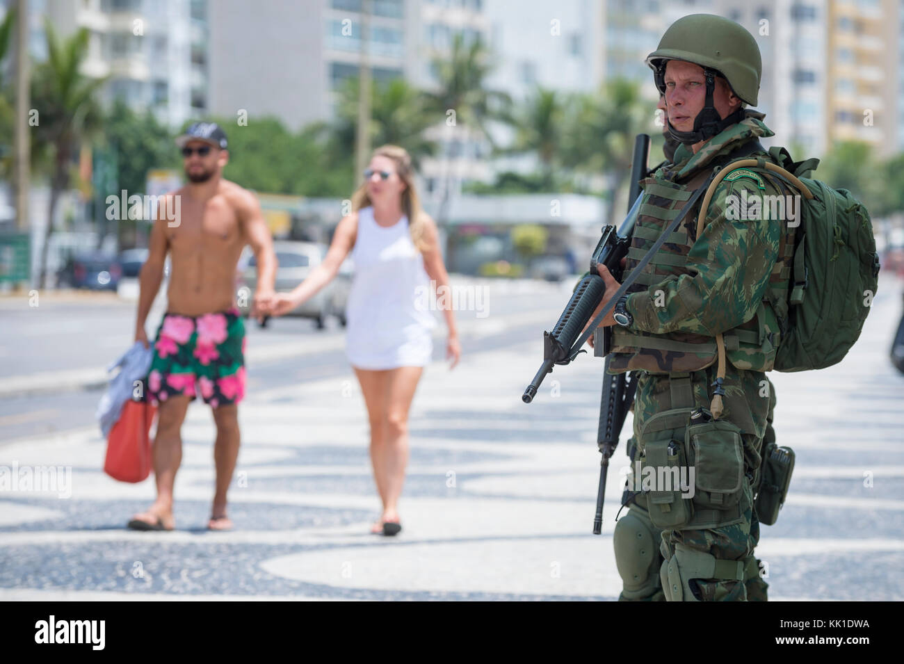 RIO DE JANEIRO - FEBRUARY 10, 2017: Tourists pass Brazilian Army soldiers standing in full camouflage uniform on - Stock Image