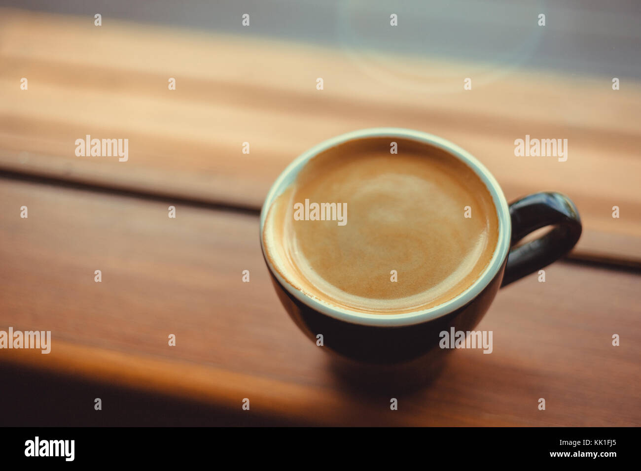 americano coffee on a side of the window in the morning, selective focus. vintage photo and film style. - Stock Image