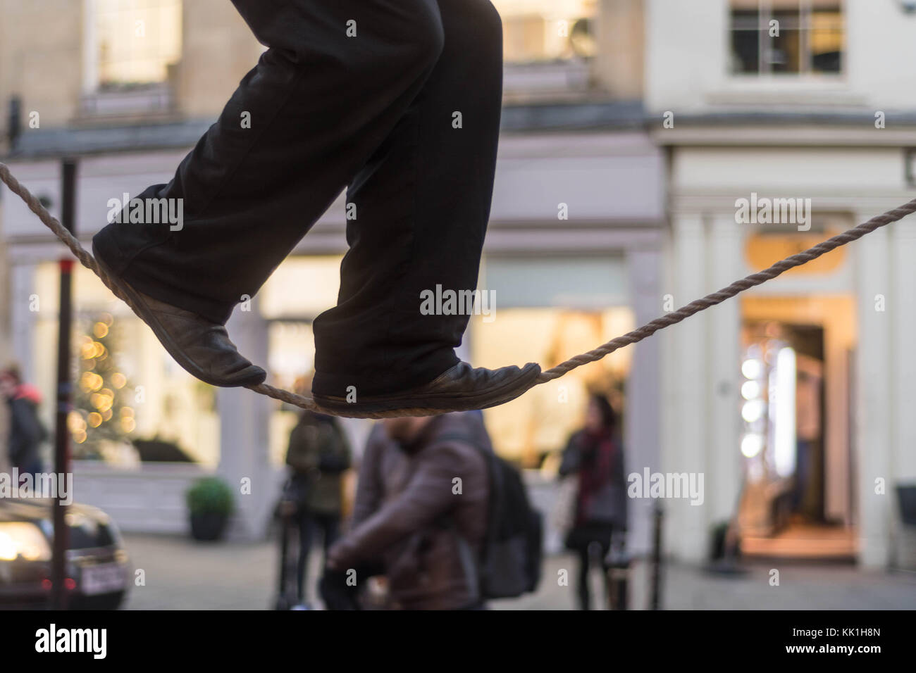 Tight rope walker's legs. Feet of acrobat balancing on rope in busy high street with passers by - Stock Image