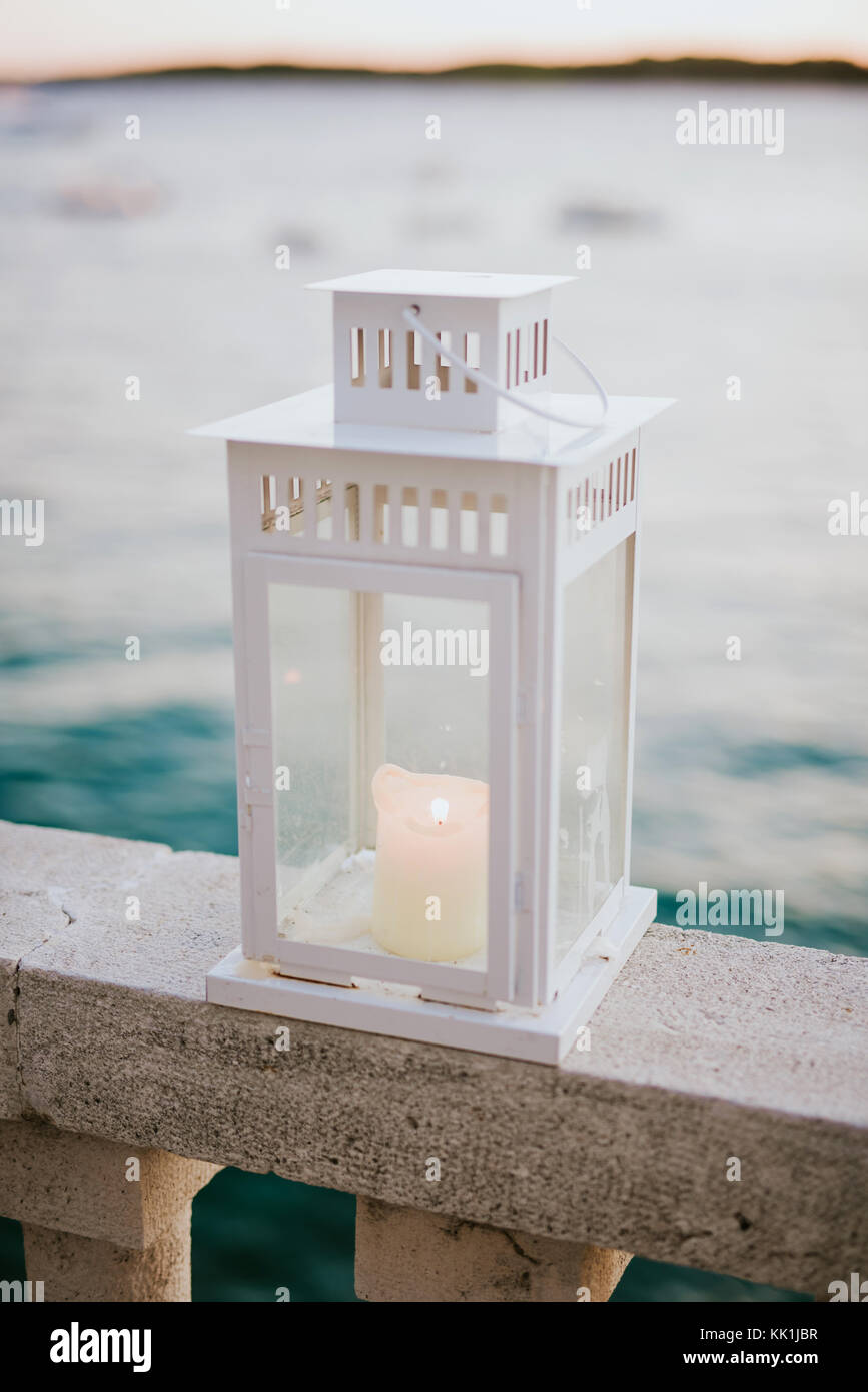 White metal lantern with burning candle glowing with sea in the background - Stock Image