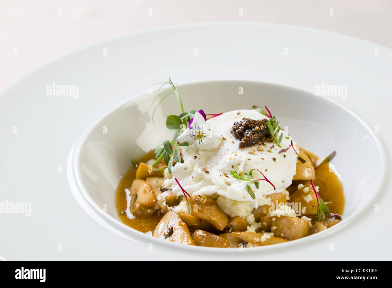 mix of mushrooms with poached egg in white plate - Stock Image