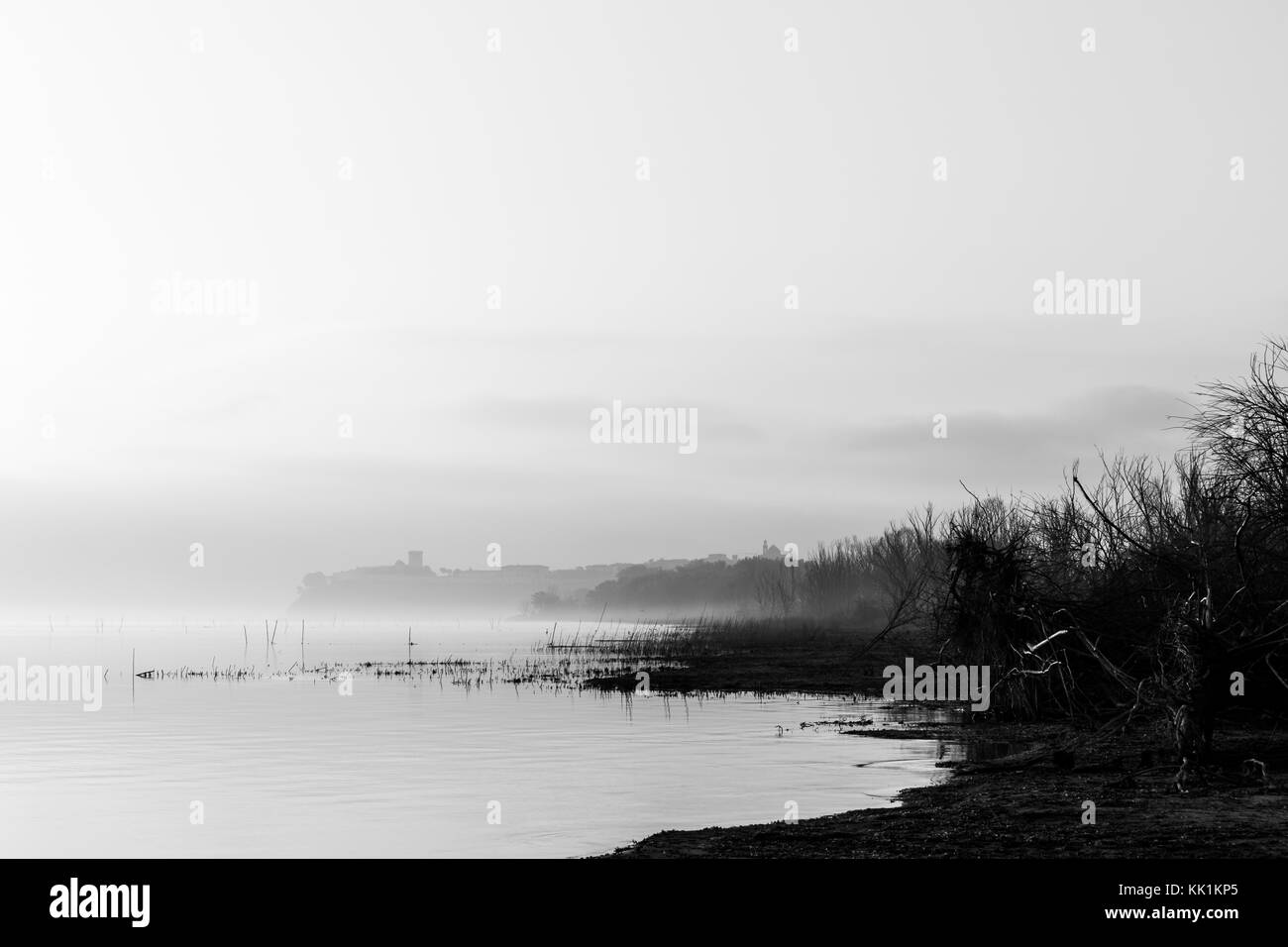 Beautiful view of Trasimeno  lake (Umbria) shore at dawn, with Castiglione del Lago town in the mist in the background - Stock Image