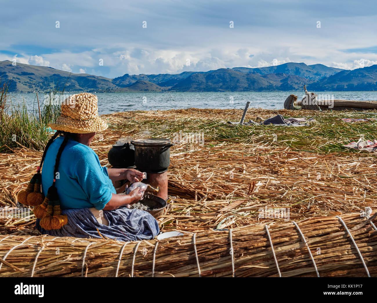 Native Uro Lady cooking, Uros Floating Islands, Lake Titicaca, Puno Region, Peru - Stock Image