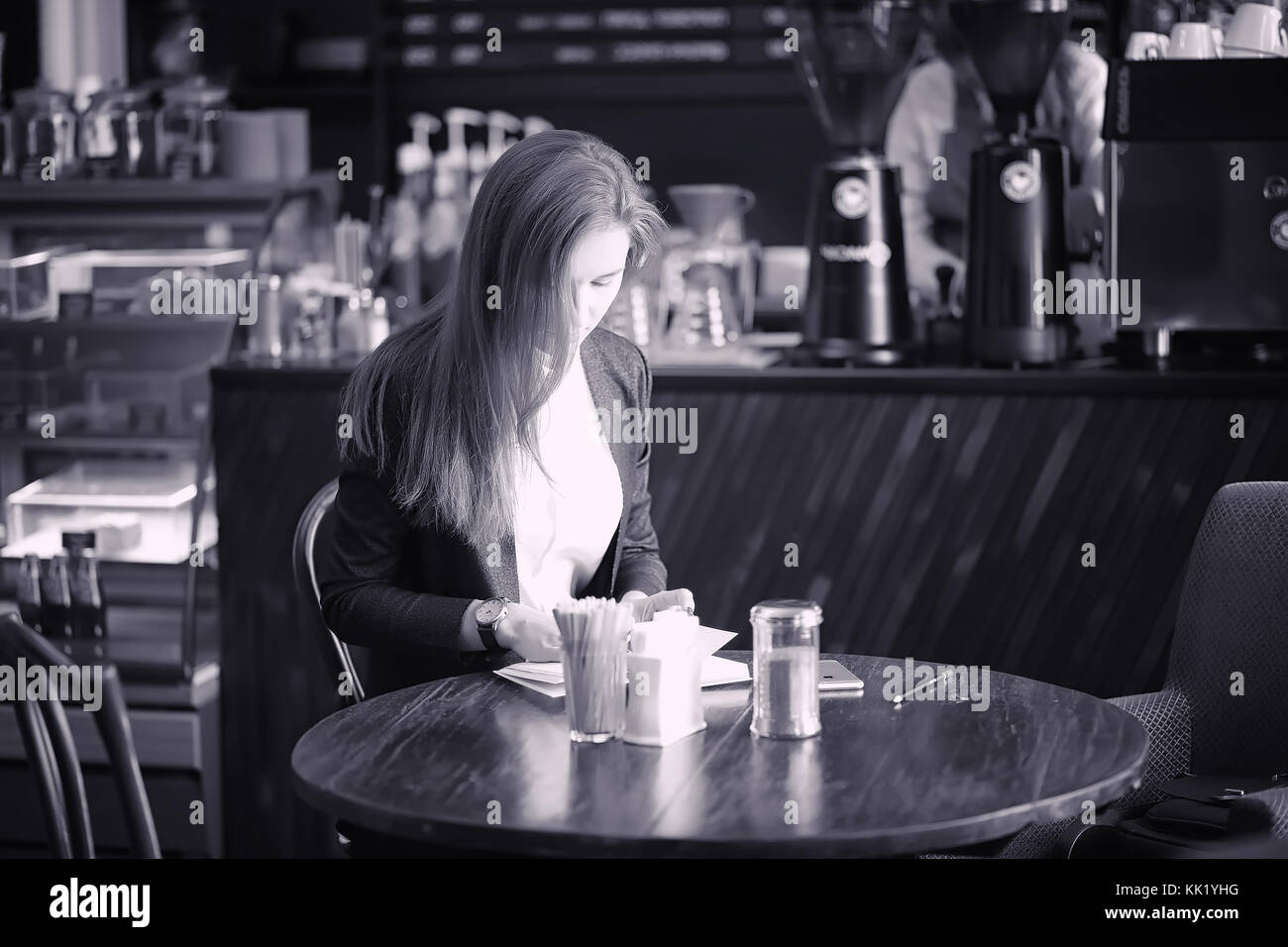A girl in a cafe is drinking coffee. A woman is having breakfast Stock Photo