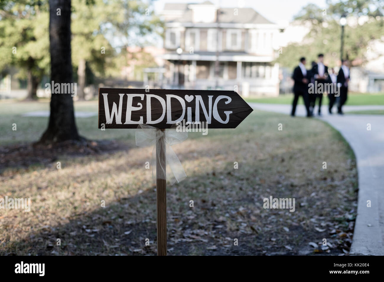 Wedding signpost arrow with white veil, groomsmen in the background - Stock Image