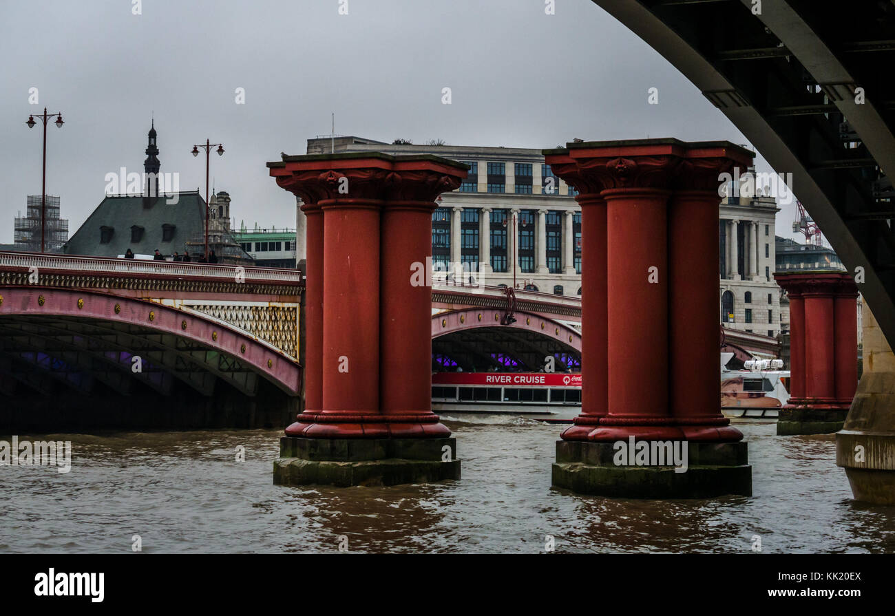 Disused Victorian bridge posts of Victorian Blackfriars railway bridge, with Unilever House, River Thames, London, - Stock Image