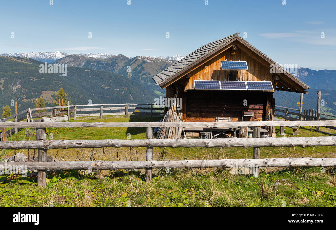 Wooden shepherd lodge with solar panels on a highland pasture with Alpine mountain landscape in Western Carinthia, Stock Photo