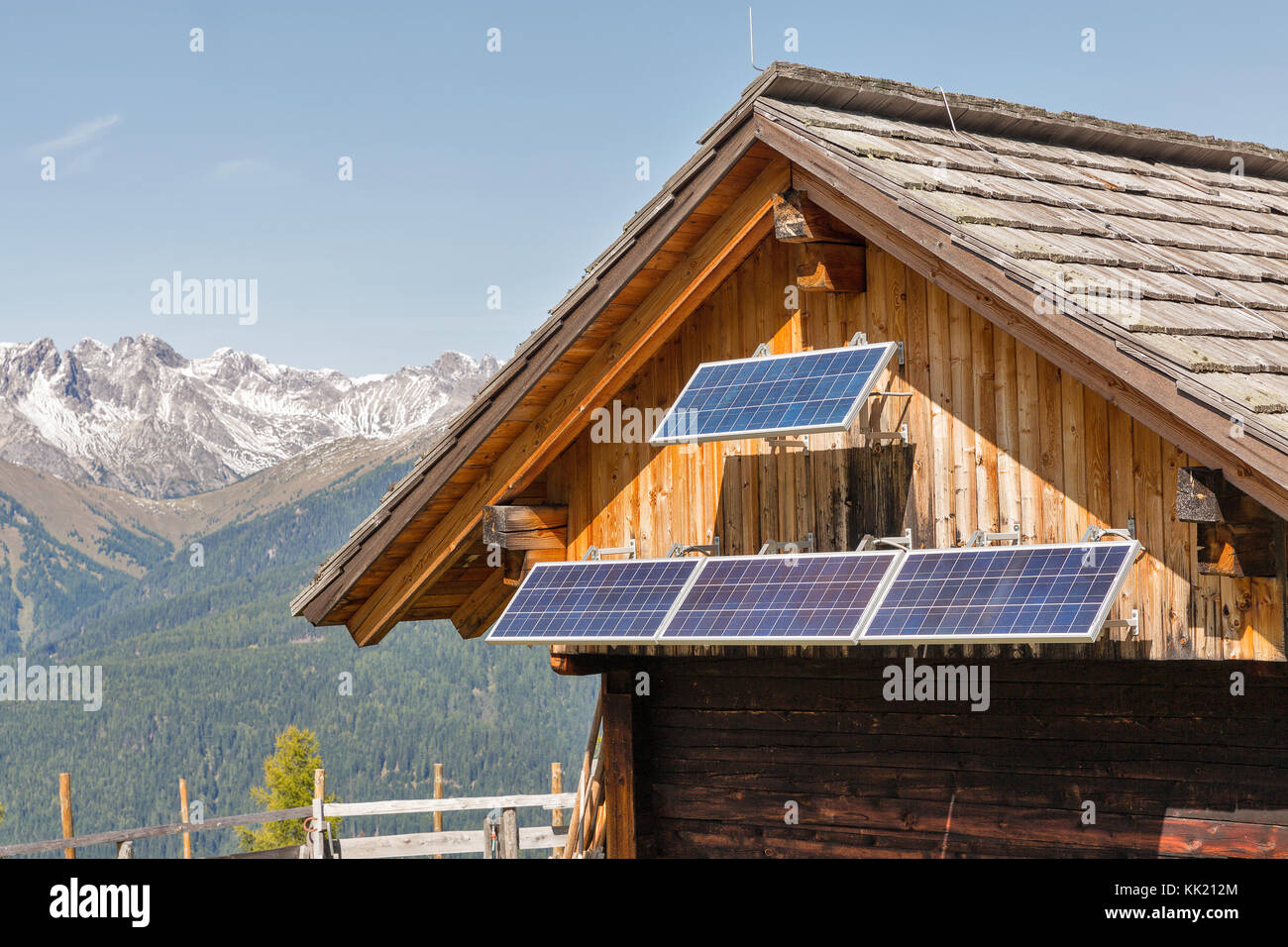 Wooden shepherd lodge with solar panels with Alpine mountain landscape in Western Carinthia, Austria. Stock Photo